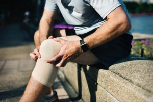 Man sitting on bench grabbing knee as a sign of pain