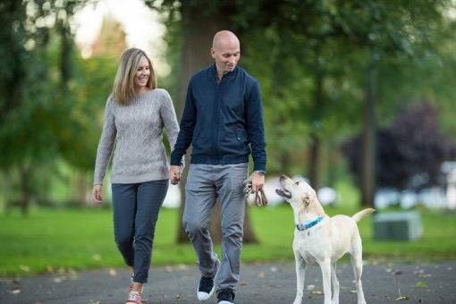 Young couple walking in the park with dog